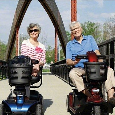 Couple both riding mobility scooters on a bridge